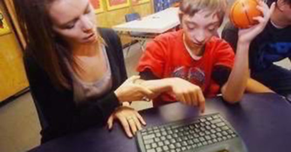 Facilitator typing with disabled boy.